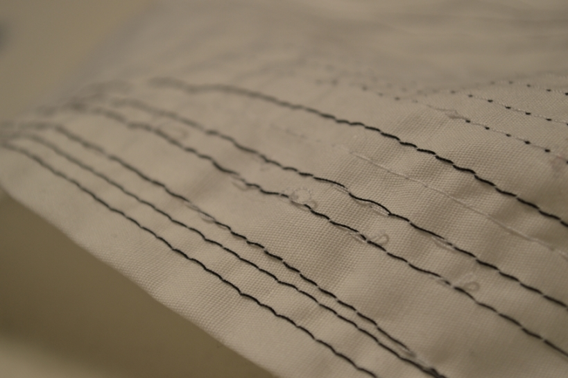 The black thread is the bobbin thread and the white is the needle thread.