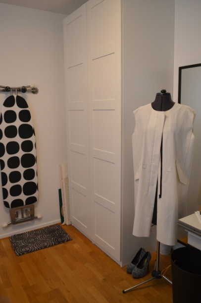 The hanger on the wall also works as storage for the ironing board