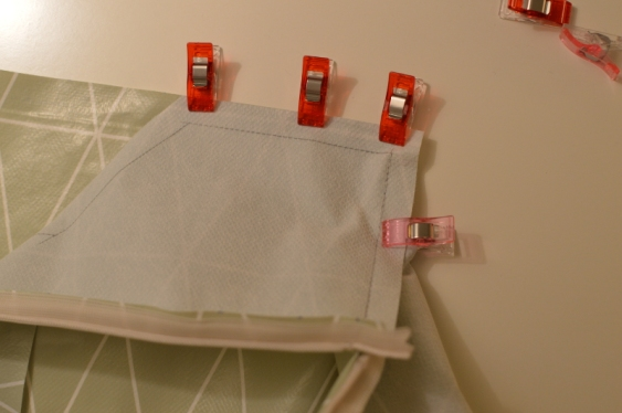 """""""Clip"""" and sew one stretch at a time (red clips). The pink clip to the right just keeps the oil cloth in place."""